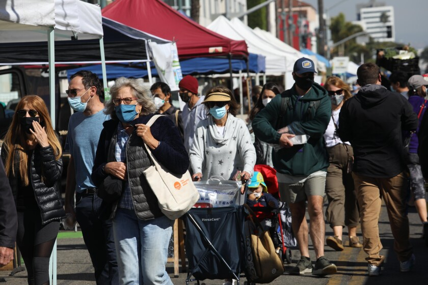 SANTA MONICA, CA - NOVEMBER 11, 2020 - Customers, wearing masks, shop for produce to buy at the Santa Monica Farmer's Market along Arizona Street in Santa Monica on November 11, 2020. (Genaro Molina / Los Angeles Times)