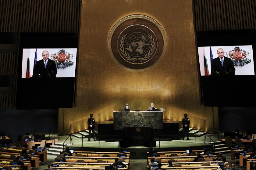Bulgaria's President Rumen Radev is seen on video screens as he addresses the 76th Session of the United Nations General Assembly remotely, Tuesday, Sept. 21, 2021 at U.N. headquarters. (Spencer Platt/Pool Photo via AP)
