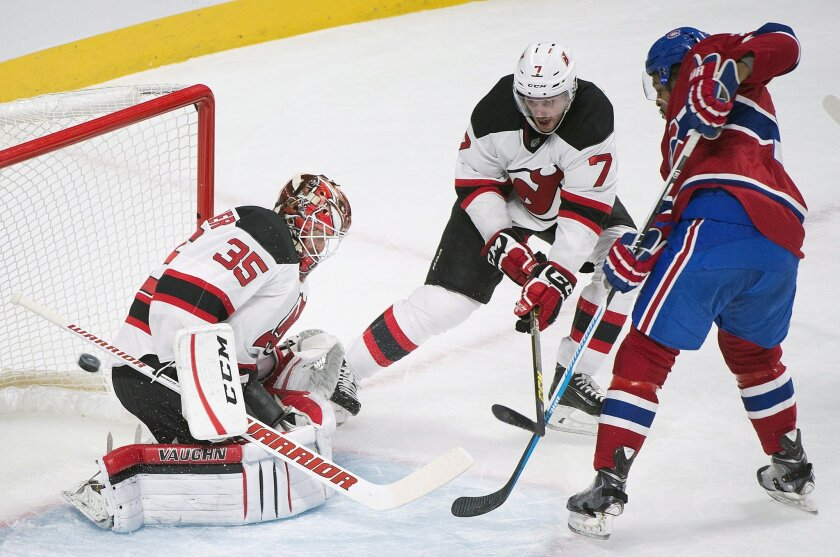 New Jersey Devils' goalie Cory Schneider makes a save against Montreal Canadiens' Devante Smith-Pelly, right, as the Devils' Jon Merrill (7) defends during the first period of an NHL hockey game, in Montreal, Saturday, Nov. 28, 2015. (Graham Hughes/The Canadian Press via AP) MANDATORY CREDIT