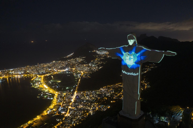 """En esta imagen, tomada el 3 de mayo de 2020, la icónica estatua del Cristo Redentor iluminada como si llevase una mascarilla y con la frase """"Mascarillas salvan"""" (en portugués), durante la pandemia del coronavitus, en Río de Janeiro, Brasil. (AP Foto/Leo Correa)"""