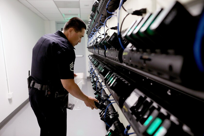 A police officer takes a body camera from a rack