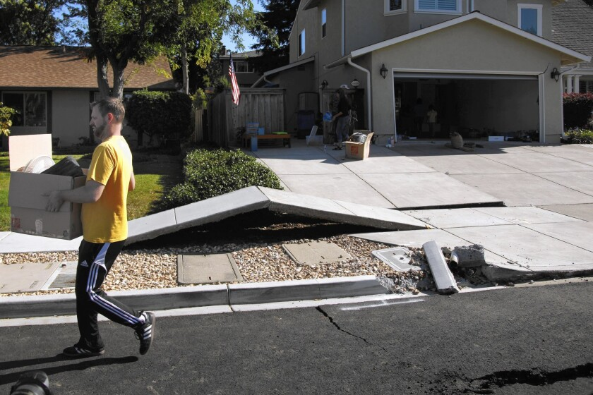 Scott Whitlock walks over a stretch of buckled sidewalk while helping his parents move out of their damaged home. The fault line was unknown to geologists before it ruptured in August.