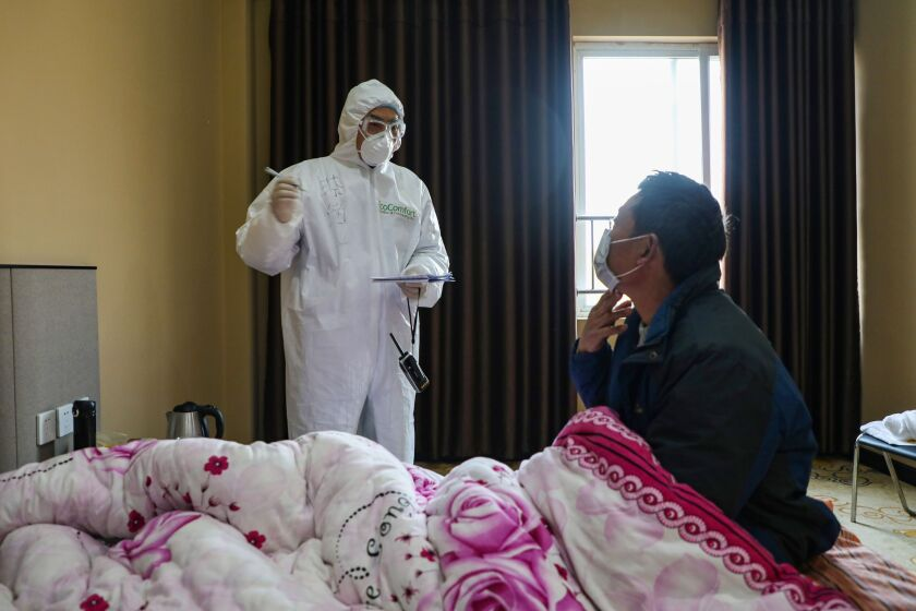 A doctor talks with a patient Feb. 3 during rounds of a quarantine ward in Wuhan, China.