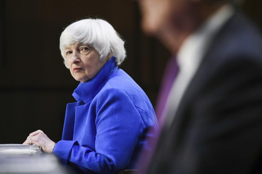 Treasury Secretary Janet Yellen listens to a person speak nearby.