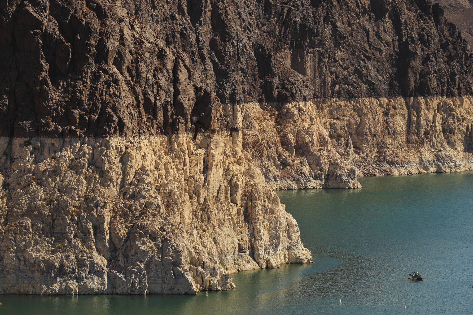 Un persona observa de cerca las marcas de agua en el lago Mead -evidencia de su bajo nivel-