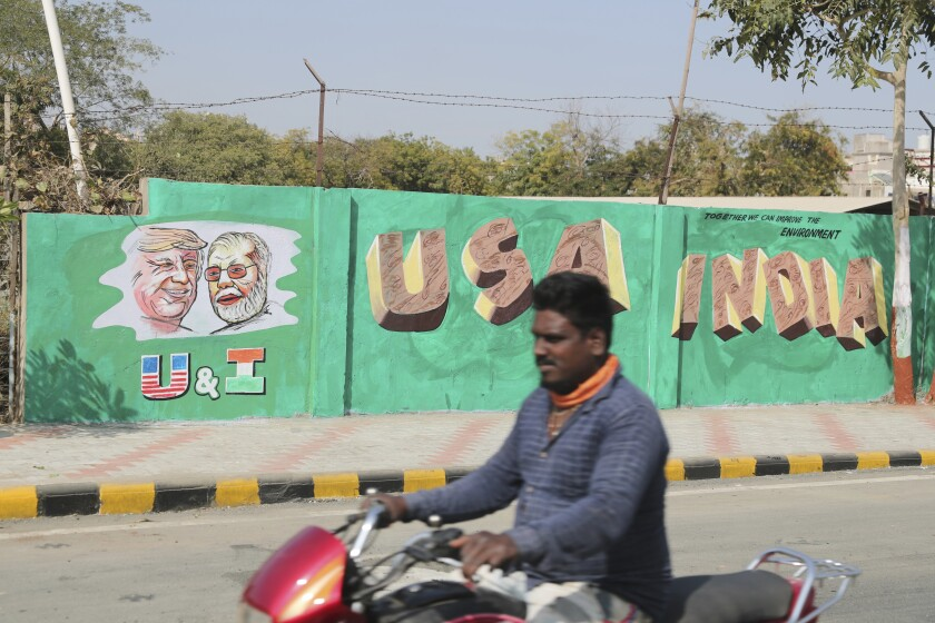 A man rides past a wall painted with portraits of U.S. President Trump and Indian Prime Minister Narendra Modi in Ahmadabad, India, on Tuesday. Trump is scheduled to visit the city next week.