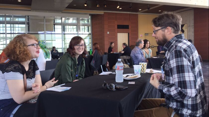 """Maddy Spangler, left, and Grace Bruinsslot get the scoop on filmmaking from Bill Perrine during the """"Human Library"""" event at the San Diego Central Library."""