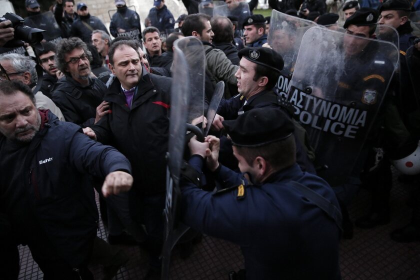 Leftist protesters, angered by years of economic austerity imposed by the European Union, scuffle with riot police on the outskirts of Athens, where they defied an 18-hour ban on demonstrations during ceremonies marking the start of Greece's six-month presidency of the bloc.