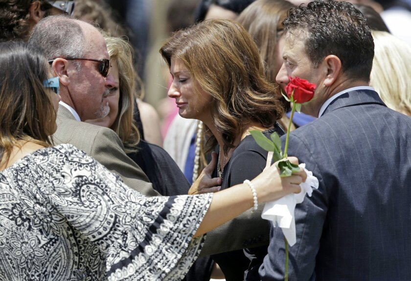 Dondie LeBlanc Breaux, mother of Mayci Breaux, center, and Kevin Breaux, right, father of Mayci, are comforted outside the Church of the Assumption, after her funeral in Franklin, La., Monday, July 27, 2015. She was one of two people killed in Thursday's movie theater shooting in Lafayette, La. (AP Photo/Gerald Herbert)