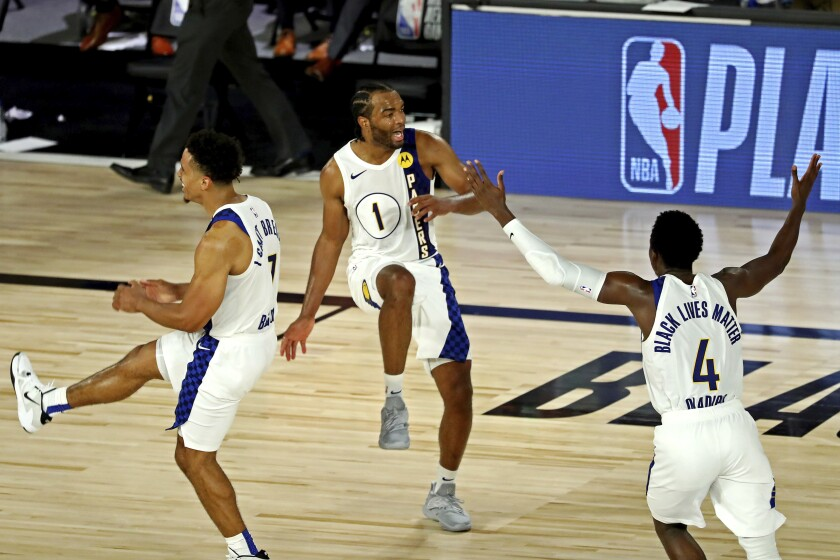 Indiana Pacers forward T.J. Warren (1) celebrates with guards Malcolm Brogdon (7) and Victor Oladipo (4) after a play against the Los Angeles Lakers during an NBA basketball game Saturday, Aug. 8, 2020, in Lake Buena Vista, Fla. (Kim Klement/Pool Photo via AP)