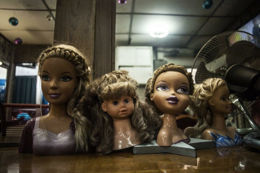 This June 12, 2015 photo shows hair styling doll heads on a counter at a hair salon in downtown San Salvador, El Salvador. Salvadoran women are giving up their blonde hair and highlights and dying it all black out of fear. The word on the street is that only the girlfriends of gang members are allo