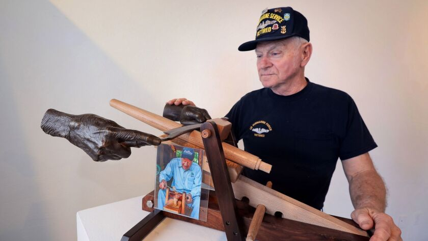 Artist Russ Filbeck has his hand on a casting of his own hand pulling a drawknife tool, shared with a casting of former President Jimmy Carter's hand, at left. The hands are pulling the tool to shape the leg for a chair.