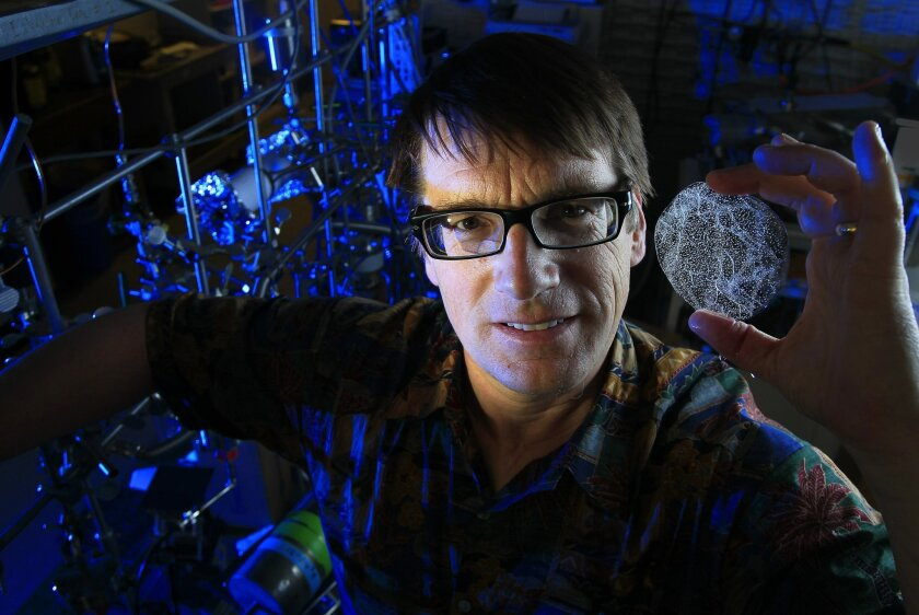 Dr. Jeff Severinghaus, a professor of geosciences at Scripps Institution of Oceanography, displays an ice core with trapped bubbles of gases he studies to track changes in ancient climate at Scripps on Friday in San Diego, California.