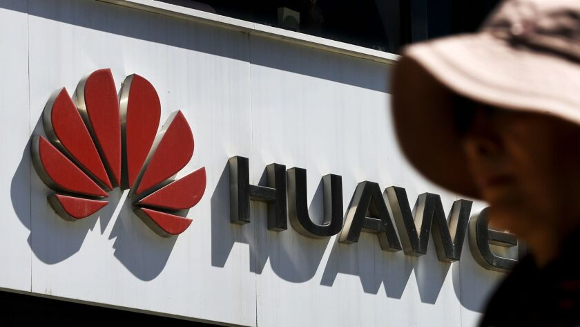 FILE - In this May 29, 2019, file photo, a woman walks by a Huawei retail store in Beijing. The worl