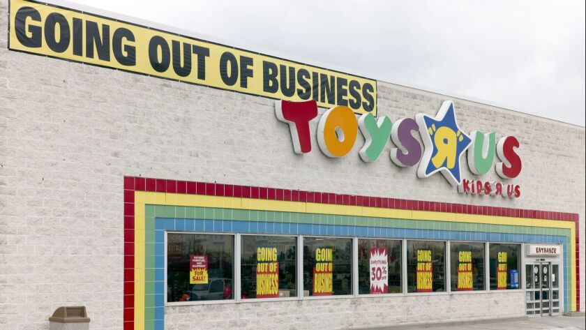 "A ""Going Out Of Business"" sign hangs over the Toys R Us store logo in Omaha, Neb., Monday, April 9,"