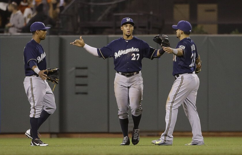 Milwaukee Brewers left fielder Khris Davis, left, center fielder Carlos Gomez (27) and left fielder Gerardo Parra celebrate after beating the San Francisco Giants 5-2 in a baseball game in San Francisco, Tuesday, July 28, 2015. (AP Photo/Jeff Chiu)