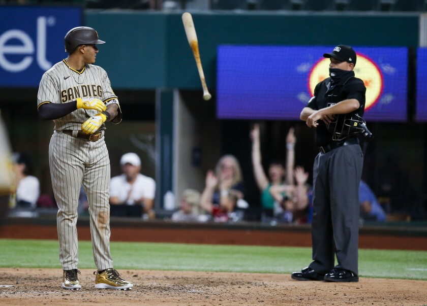 The Padres' Manny Machado, left, tosses his bat as he looks at home plate umpire Jansen Visconti