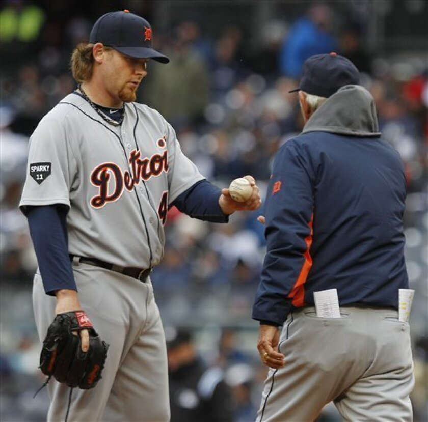Detroit Tigers relief pitcher Phil Coke hands the ball to Detroit Tigers manager Jim Leyland during the seventh inning of a baseball game against the New York Yankees Thursday, March 31, 2011, at Yankee Stadium in New York. The Tigers lost the game 6-3. (AP Photo/Frank Franklin II)