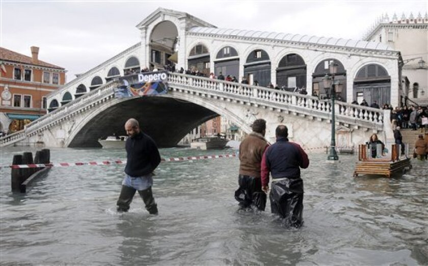 People wade through high water by Venice's Rialto Bridge, northern Italy, Monday, Dec. 1, 2008. Water in Venice has risen to its highest level in more than 20 years, leaving much of the Italian city under floods and forcing residents and tourists to wade through knee-high water. City officials say the sea level topped 156 centimeters (61 inches) on Monday, well past the 110 centimeter (40 inch) flood mark, with most streets submerged. (AP Photo/Luigi Costantini)