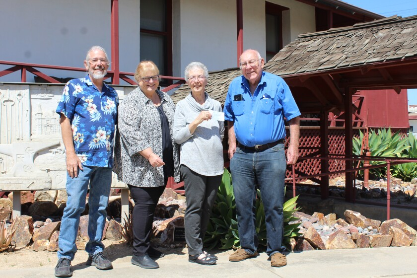 Ramona Woman's Club's Darlene McNeal presents Ramona Pioneer Historical Society President Mischa Dobrotin with a $500 check.