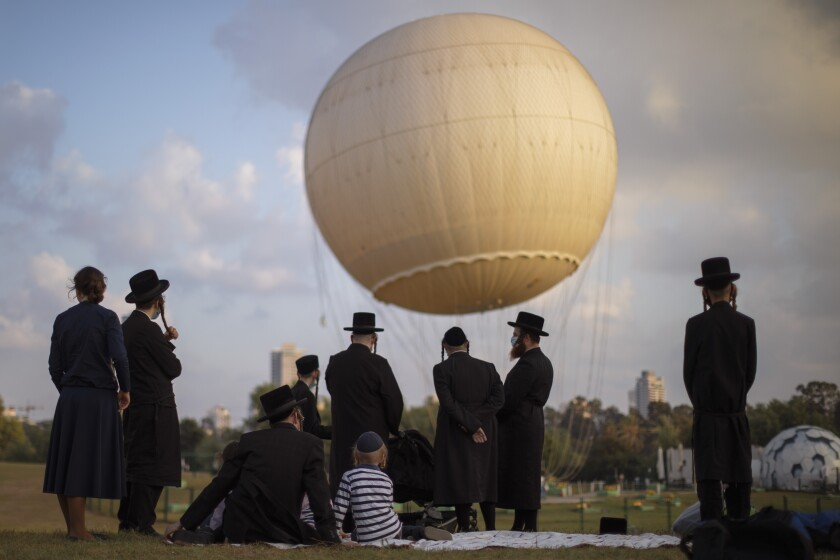 """Ultra-Orthodox Jews, some wearing protective face masks amid concerns over the country's coronavirus outbreak, spend the day at a park in Tel Aviv, Israel, Wednesday, Aug. 12, 2020. Ultra-Orthodox Yeshivas students enjoy Bein Hazmanim (""""between the times"""") for two weeks of summer vacation. (AP Photo/Oded Balilty)"""