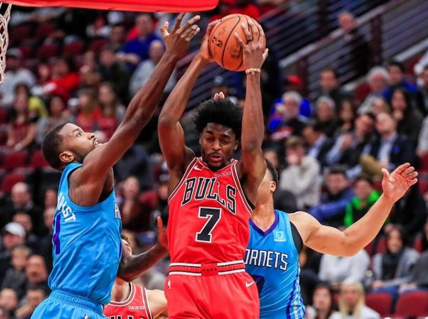 Justin Holiday (c) de Bulls lanza sobre Miles Bridges (d) y Michael Kidd-Gilchrist (i) de Charlotte Hornets hoy, miércoles 24 de octubre de 2018, en un juego de la NBA entre Charlotte Hornets y Chicago Bulls en United Center en Chicago (EE.UU.). EFE