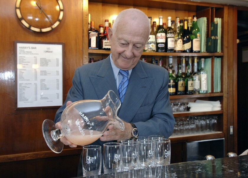 Arrigo Cipriani pours peach juice into Champagne flutes while making Bellinis at Harry's Bar in Venice in 2006.