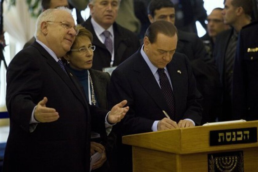 "Reuven Rivlin, the Speaker of the Knesset, Israel's parliament, gestures as Italian Prime Minister Silvio Berlusconi signs the Knesset guest book during a ceremony in Jerusalem, Wednesday, Feb. 3, 2010. Berlusconi told Israel's parliament on Wednesday that the world ""cannot make compromises"" and must close ranks to ""resist the dangerous aims of the Iranian regime."" (AP Photo/Bernat Armangue, Pool)"