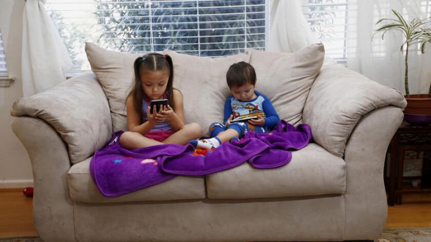 PIE DE FOTO: Juliana Sánchez, de 5 años y su hermano Francisco de 2, miran programación infantil en YouTube, desde los celulares de sus padres en su casa de Mountain House en California. (Gary Reyes/Bay Area News Group/TNS).