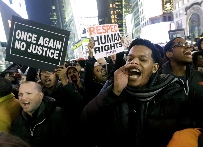 Protestors shout at Times Square after it was announced that the New York City police officer involved in the death of Eric Garner is not being indicted, Wednesday, Dec. 3, 2014, in New York. A grand jury cleared the white New York City police officer Wednesday in the videotaped chokehold death of