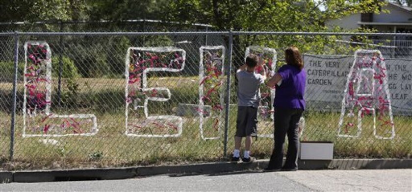 Teacher Cecilia Richardson helps a student tie a ribbon honoring murder victim, third grader Leila Fowler, at Jenny Lind Elementary School in Valley Springs, Calif., Monday April 29, 2013. Authorities are searching for the killer of Fowler, 8, who was found murdered by her 12-year-old brother in the family's Valley Springs home Saturday. (AP Photo/Rich Pedroncelli)