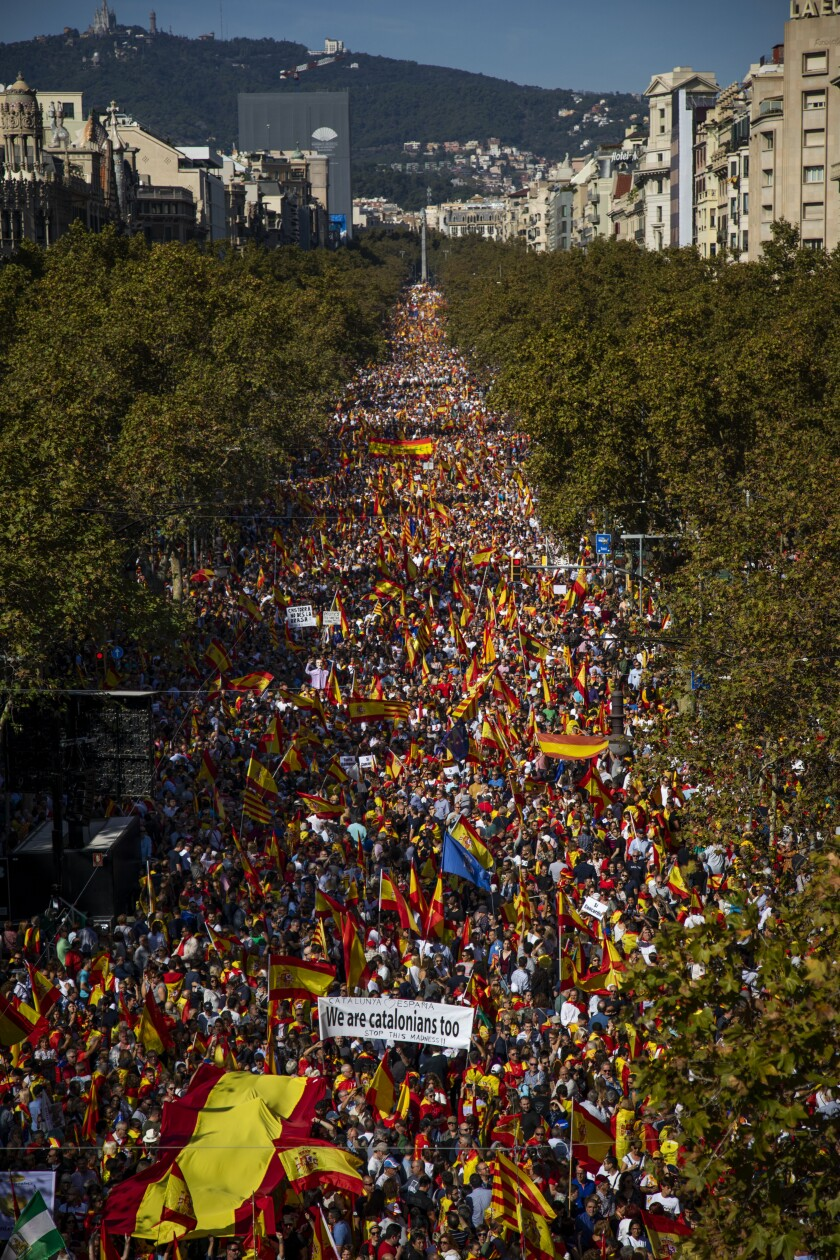 In this photo taken on Sunday, Oct. 27, 2019, Pro-Spain demonstrators gather a long a street during a protest called by a unionist Catalan civil society group in Barcelona, Spain. Catalans who want the restive region to remain part of Spain are becoming increasingly frustrated with the chaos, disruptions and violence brought by a renewed wave of pro-independence protests triggered by prison sentences against leaders of a failed bid for secession in 2017. (AP Photo/Emilio Morenatti)