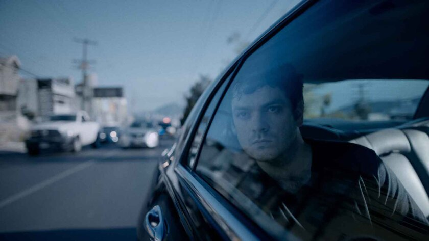A man looks out of a car's backseat window.