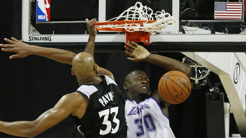 Lakers forward Julius Randle, right, dunks over Minnesota Timberwolves forward Adreian Payne during an NBA summer league game in Las Vegas on July 10.