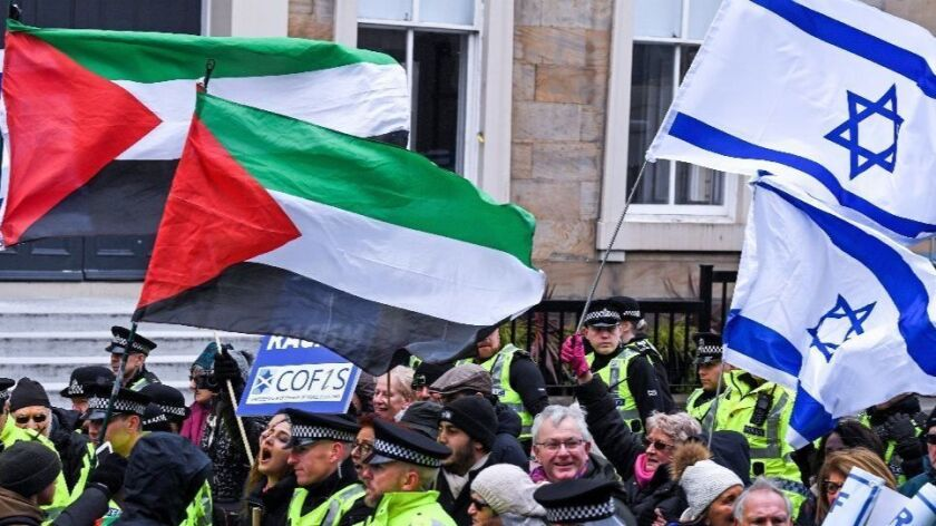 Palestinian and Israeli flags fly as rival protesters face off.