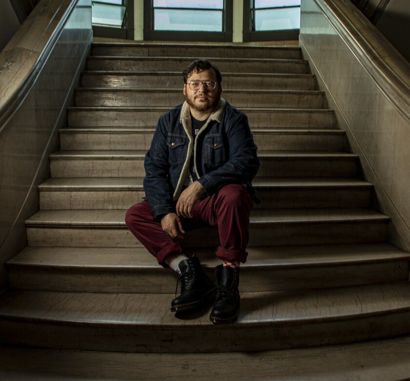 christopher oscar peña sits on the interior steps of an apartment building.