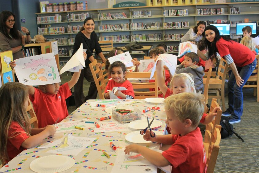 These pre-kindergarten students, who made some of the art on the wall, make more at the library!