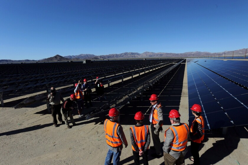 Officials tour a new solar power plant in Riverside County in February. While some politicians want more renewable energy in California, it can be difficult to manage.