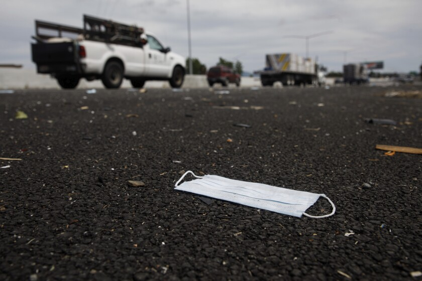 One of the spilled masks is visible on the shoulder of southbound Interstate 880 in Union City. In the midst of the coronavirus pandemic, the freeway suffered a mini-traffic jam when someone tossed hundreds of face masks onto the road and some motorists stopped to grab them, the California Highway Patrol reported.