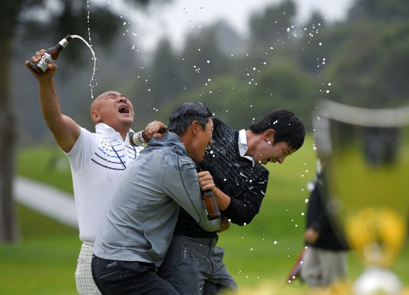 Jason Oh, left, and Noh Seung-Yul, right, pour beer on James Hahn on the 18th green after Hahn won the Northern Trust Open golf tournament on the third playoff hole at Riviera Country Club, Sunday, Feb. 22, 2015, in Los Angeles. The trophy is at right. (AP Photo/Mark J. Terrill)