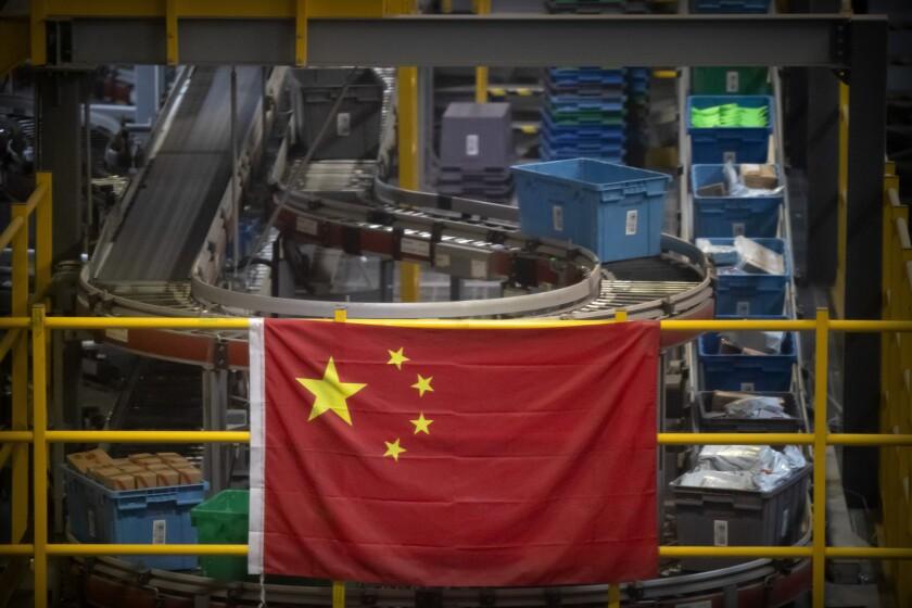 Una bandera china cuelga cerca de una línea de manejo de paquetes en un almacén de un minorista en línea en Beijing.