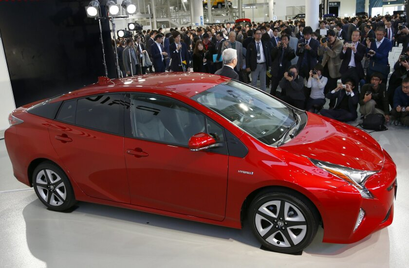 Toyota Motor Corp. Executive Vice President Mitsuhisa Kato poses with a Toyota new Prius  at the automaker's showroom in Tokyo, Wednesday, Dec. 9, 2015. Sales for the Prius dropped 10.9 percent in 2015, marking the first time annual sales were down since the hybrid was introduced in 1997. (AP Photo