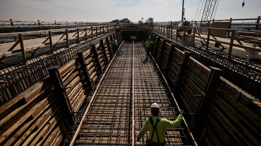 California's high-speed rail project has been dogged by schedule setbacks and cost overruns. Here, workers construct a 3,700-foot viaduct to extend over State Route 99 in Fresno County.