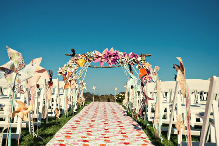 """The """"altar"""" where the bride and groom got married at this Jesi Haack Design wedding at a winery in Malibu was adorned with brilliant paper flowers, pinwheels and kites."""