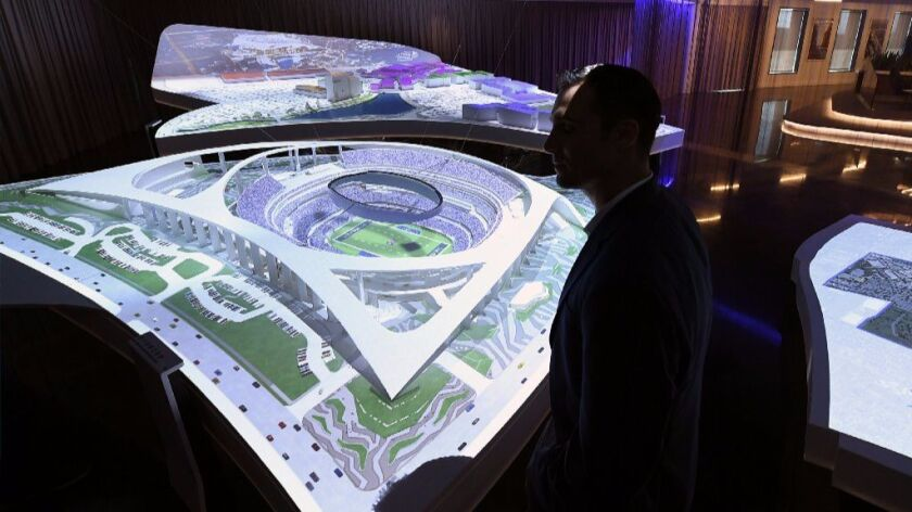 Greg Kish, vice-president of sales and service for L.A. stadium, stands next to a model of the futur