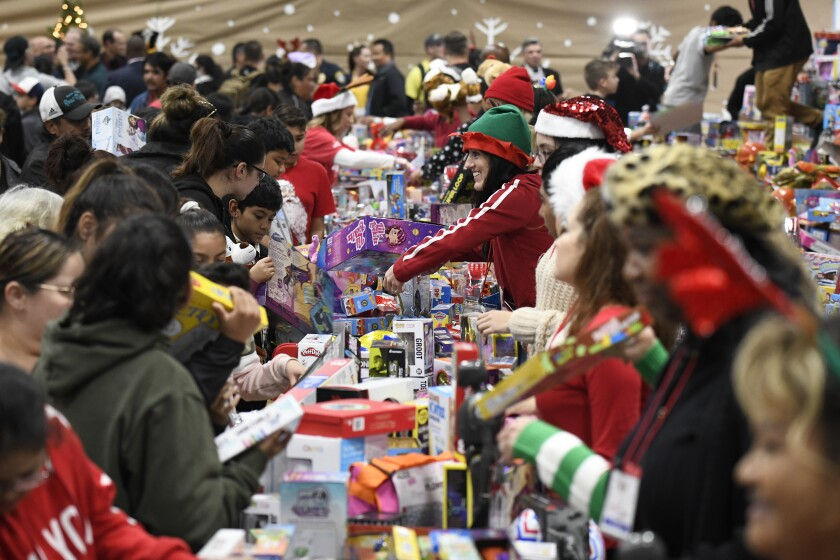 Volunteers, right, hand out toys to families, left, in the Toy Room at the Toys for Joy event held at Lincoln High School Saturday.