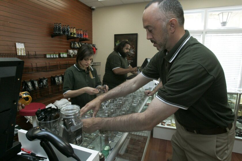 """Zach Lazarus, right, COO of """"A Green Alternative"""" medical marijuana dispensary in Otay Mesa, labeled bottles just before the opening of their office March 18.."""