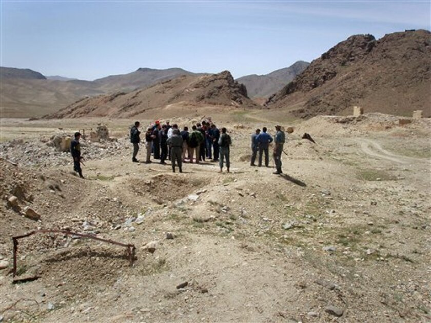 "This April 2007 photo provided by James Yeager shows a delegation from the state-owned Chinese company, China Metallurgical Group Corporation, visiting the site of a copper mine in Aynak, a former al-Qaida stronghold southeast of Kabul, Afghanistan. The mounds behind the group, called ""outcrops"", signal the large quantity of copper that lies below. Yeager says a handful of Afghan officials dominated a secretive selection process that gave MCC improbably high marks over firms from the U.S., Canada and other countries, to develop a mine to tap one of the world's largest unexploited copper reserves. (AP Photo/James R. Yeager)"