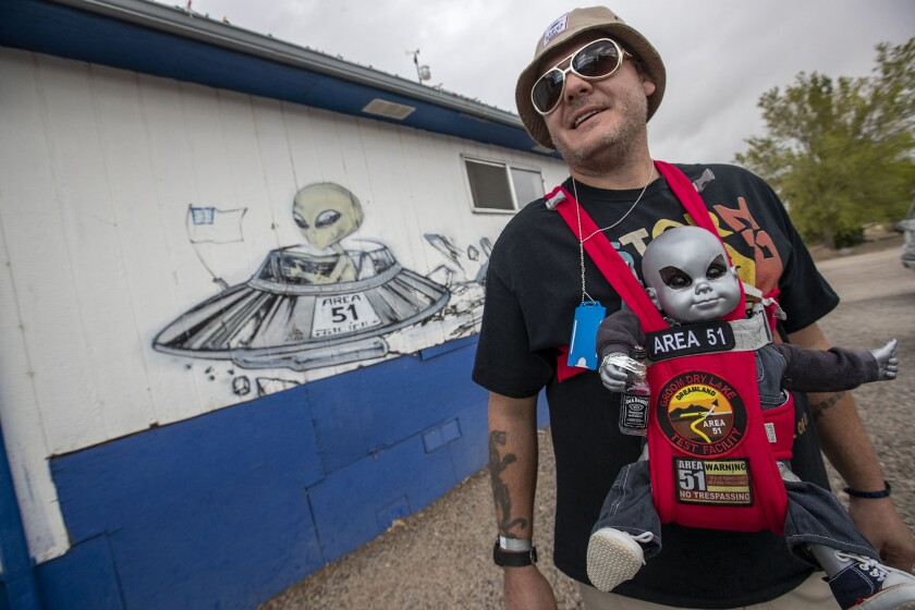 Alien enthusiast Rob Kulas of Chicago carries an alien baby doll around the Little A'Le'Inn grounds in the Area 51-adjacent town of Rachel, Nev.