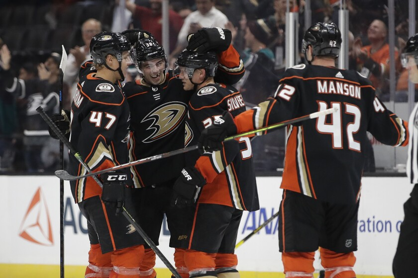 Ducks' Jakob Silfverberg, second from right, is hugged by teammates after scoring against the Buffalo Sabres during the third period on Wednesday at Honda Center.